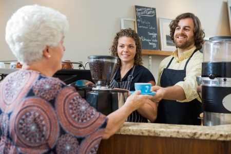 counter service: Mid adult waitress with colleague serving coffee to senior woman at counter in cafe