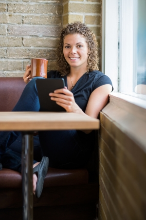 Full length portrait of smiling woman with digital tablet and coffee mug in cafeteria photo