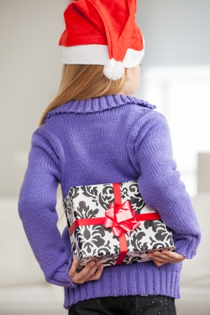 gift behind back: Rear view of girl in Santa hat hiding Christmas gift behind back at home Stock Photo