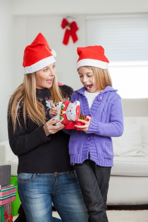 Surprised mother and daughter in Santa hat with Christmas gift at home photo