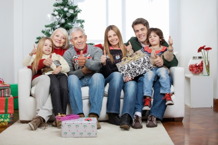 Full length portrait of multigeneration family with Christmas presents sitting on sofa at home photo