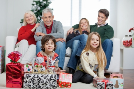 christmas morning: Portrait of happy multigeneration family with Christmas gifts sitting in house