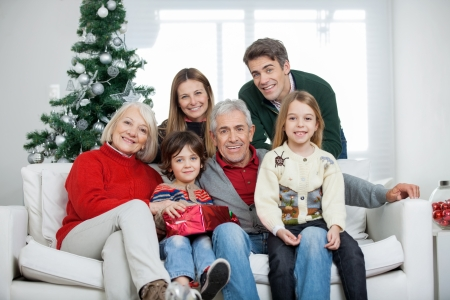 christmas morning: Portrait of happy multigeneration family with Christmas present in house Stock Photo