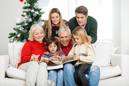 bible christmas: Happy multigeneration family reading book together in house