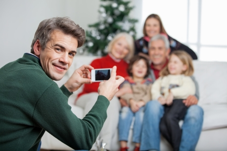 Portrait of father photographing family through mobilephone during Christmas at home photo