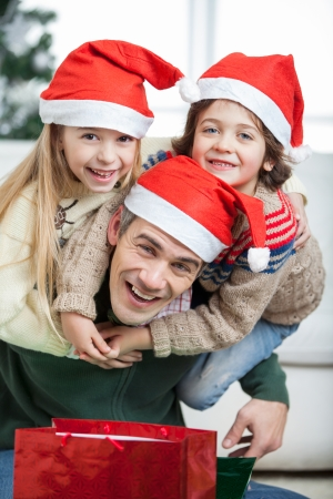 christmas morning: Portrait of playful father piggybacking children during Christmas at home Stock Photo