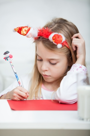 Cute girl wearing headband writing letter to Santa Claus at home photo