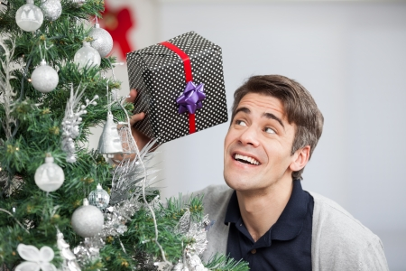 Curious mid adult man holding gift by Christmas tree at home photo