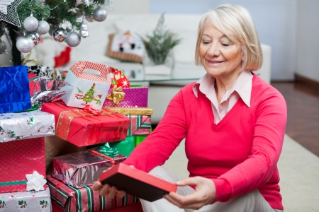 Smiling senior woman looking at Christmas gift in house photo