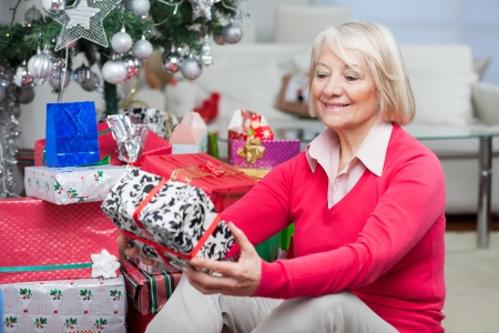 Senior woman looking at Christmas gift while sitting on floor at home photo