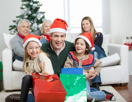 christmas morning: Portrait of happy father and children with gifts while family in background during Christmas at home Stock Photo