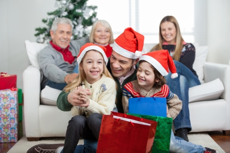 Happy children and father with gifts while family in background during Christmas at home photo