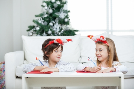 Siblings looking at each other while writing letter to Santa Claus during Christmas at home photo