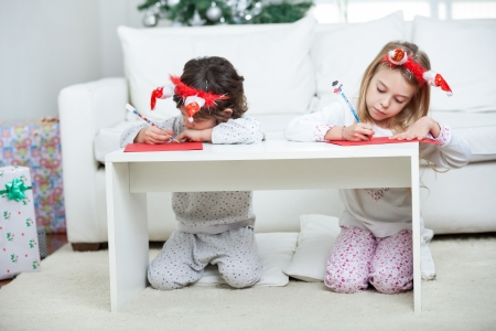 Children writing letter to Santa Claus during Christmas at home photo