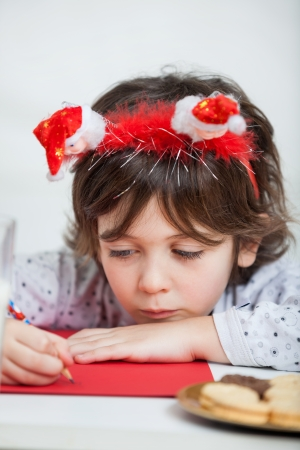 Closeup of boy wearing headband writing letter to Santa Claus at home photo