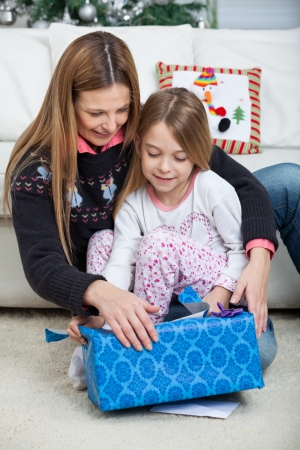 Mother and daughter opening Christmas present at home photo