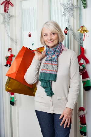 Portrait of senior woman with shopping bags standing by door during Christmas at home photo