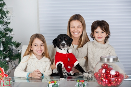 holding a christmas ornament: Portrait of happy family with pet dog sitting at home during Christmas Stock Photo