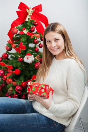 Portrait of beautiful woman with gift sitting by Christmas tree at home photo