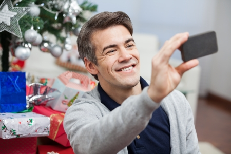 Happy man taking self portrait through smartphone during Christmas at home photo