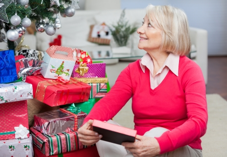 Senior woman with Christmas present looking away while sitting on floor at home photo