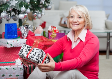 Portrait of smiling senior woman sitting by stack of Christmas presents at home photo