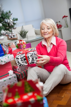 Senior woman looking at gift while sitting at home during Christmas photo