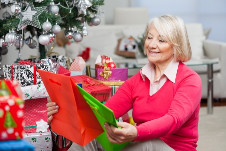 Smiling senior woman choosing bags while sitting by presents at home photo