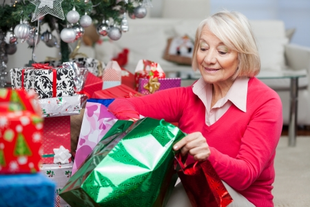 Senior woman looking in bag while sitting by Christmas presents at home photo