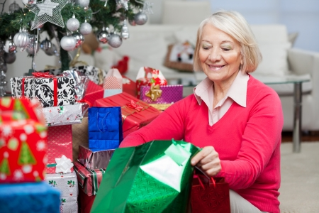 Smiling senior woman looking in bag while sitting by Christmas gifts at home photo
