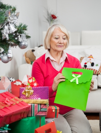 woman holding bag: Senior woman holding bag while sitting by Christmas presents at home
