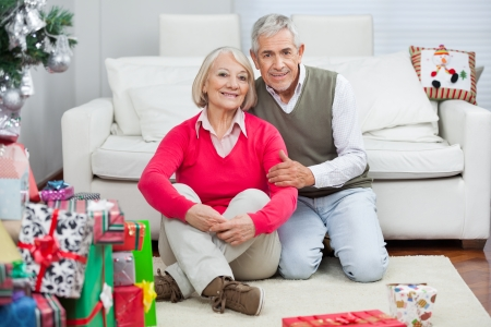Portrait of happy senior couple sitting by Christmas presents at home photo