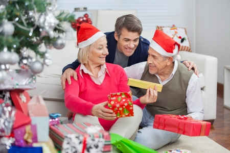 Happy parents and son with Christmas presents at home photo