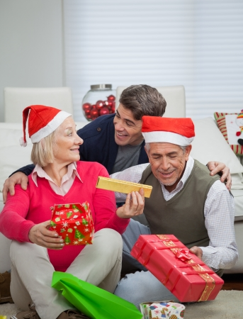 Happy family with Christmas gifts sitting on floor at home photo