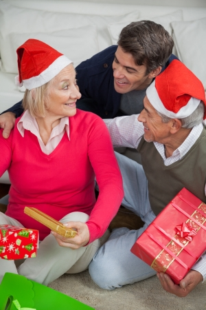 Happy son with parents holding Christmas presents at home photo