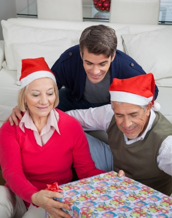 Family looking at Christmas present at home photo
