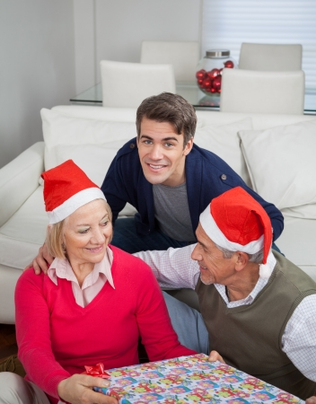 Portrait of smiling mid adult man with parents holding Christmas gift at home photo