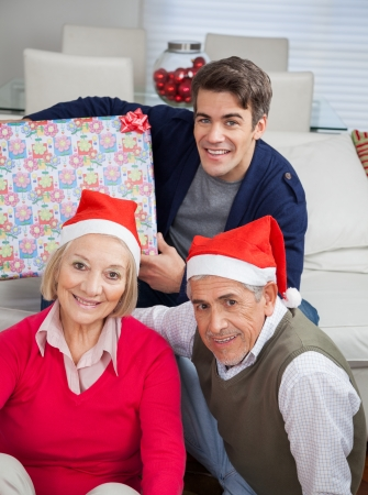 Portrait of family with Christmas present smiling together at home photo