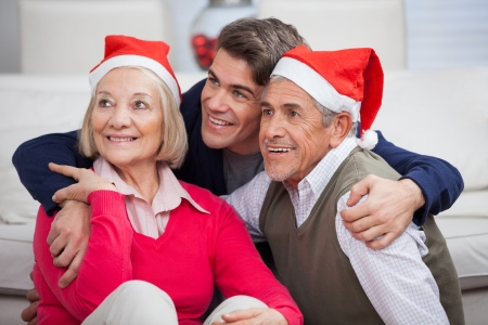 Loving son with parents wearing Santa hats looking away at home photo