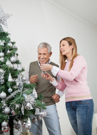 decorating christmas tree: Happy father and daughter decorating Christmas tree together at home