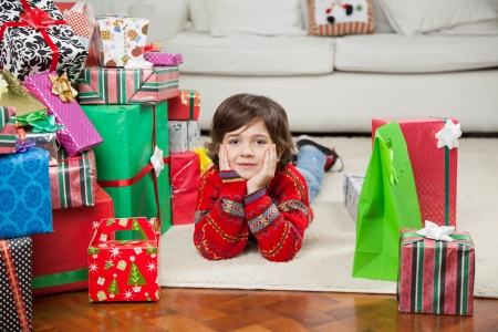 Full length portrait of cute boy lying on floor besides stacked Christmas gifts at home photo