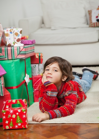 Full length portrait of cute boy lying on floor besides stacked presents at home photo