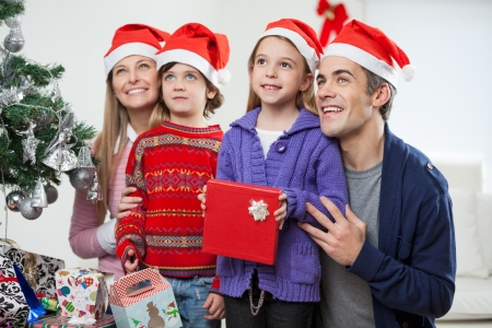 Family in Santa hats with Christmas gift looking away at home photo