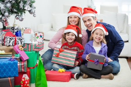 Portrait of happy family in Santa hats sitting by Christmas gifts at home photo