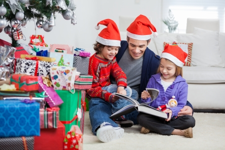 Happy siblings and father in Santa hats reading book while sitting by Christmas presents at home photo