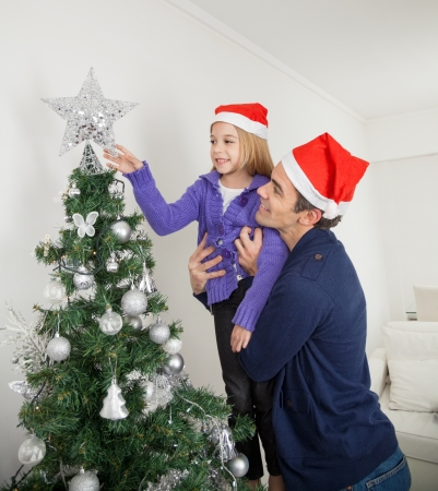 Daughter adjusting star on Christmas tree while being carried by father at home photo