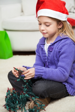 untangle: Girl in Santa hat with fairy lights sitting on floor at home during Christmas