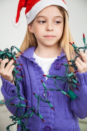untangle: Girl wearing Santa hat looking at fairy lights during Christmas in house Stock Photo