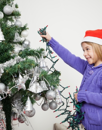 Happy girl decorating Christmas tree with fairy lights at home Stock Photo - 23801588