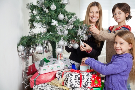 Portrait of smiling mother and siblings decorating Christmas tree at home photo